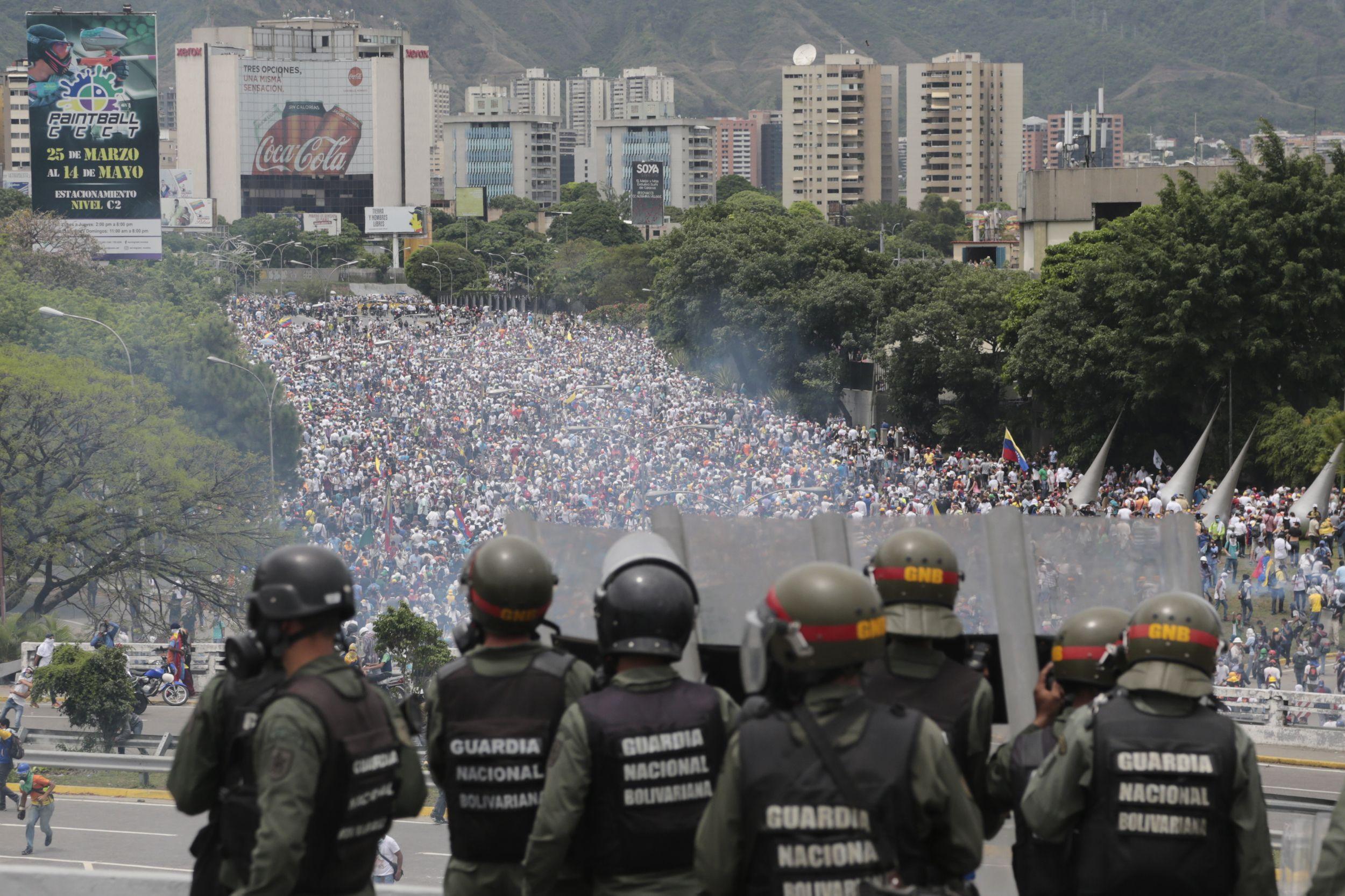 La Guardia Nacional Bolivariana observa una marcha contra el gobierno que intenta llegar a la Asamblea Nacional en Caracas. / Foto: AP