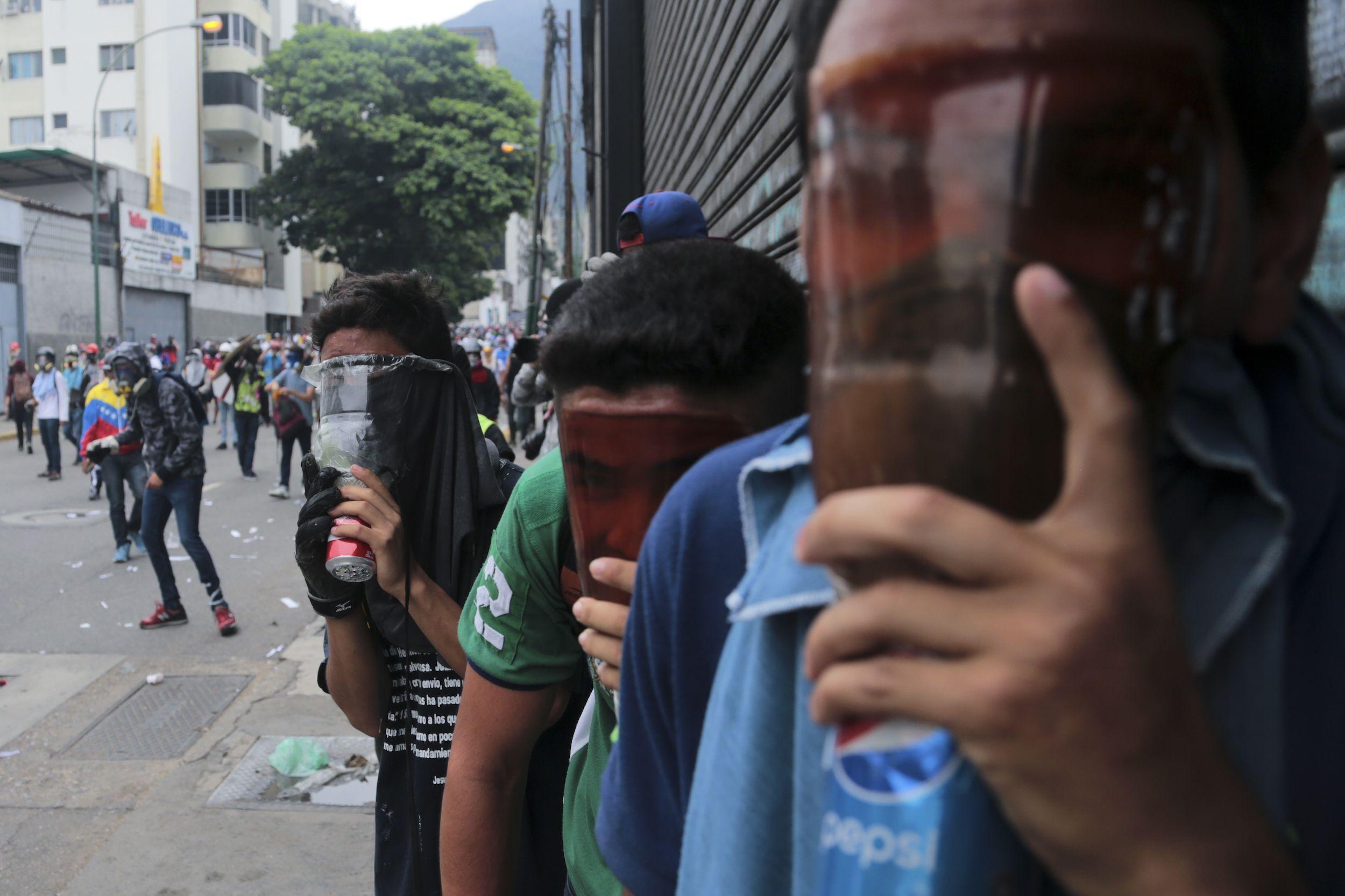 Manifestantes antigubernamentales cubren sus caras con máscaras de gas caseras durante una marcha contra el decreto del presidente venezolano Nicolás Maduro que da inicio al proceso para reformar la constitución. / Foto: AP