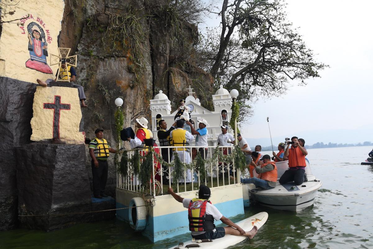 Momento en que colocan la imagen del Niños Dios en la silla de piedra a la orilla del lago. Foto: Omar Solís