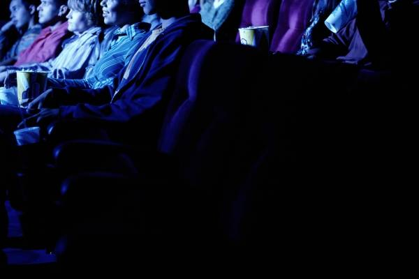 Group of young people watching movie, side view
