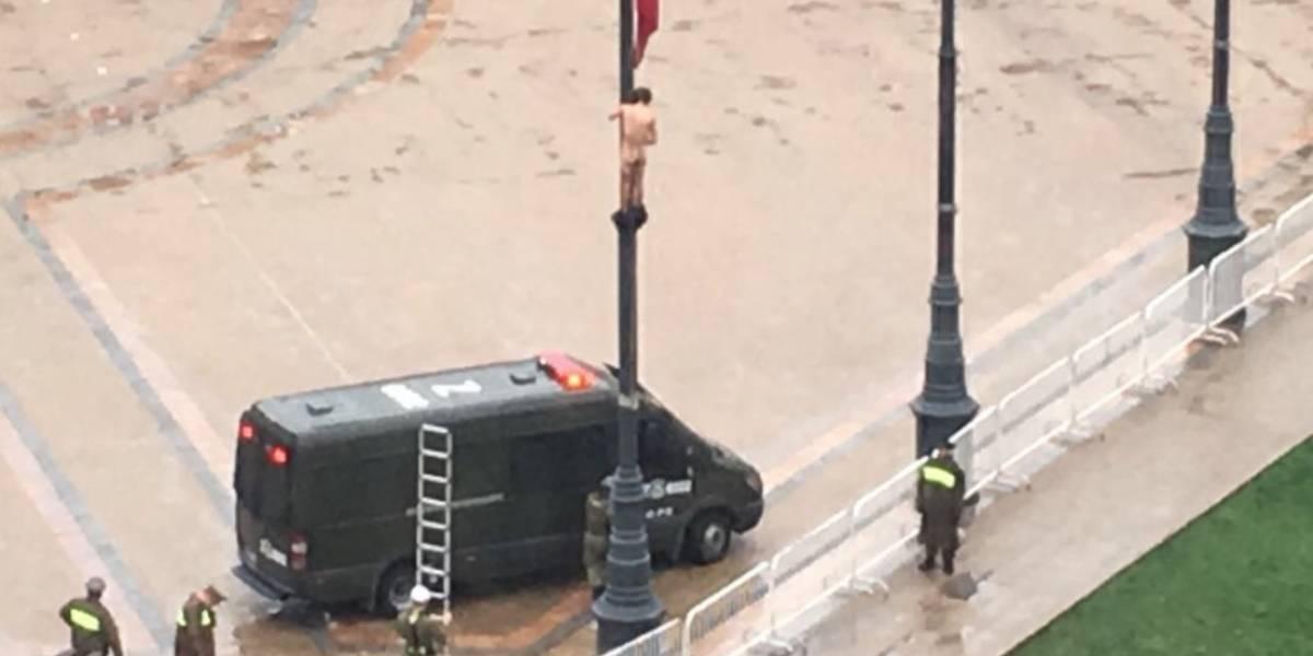 Hombre desnudo colgado desde mástil protesta frente a La Moneda y provoca revuelo en Twitter
