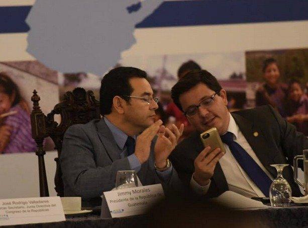 El presidente Jimmy Morales y el ministro de Finanzas, Julio Héctor Estrada conversan durante la presentación del presupuesto.