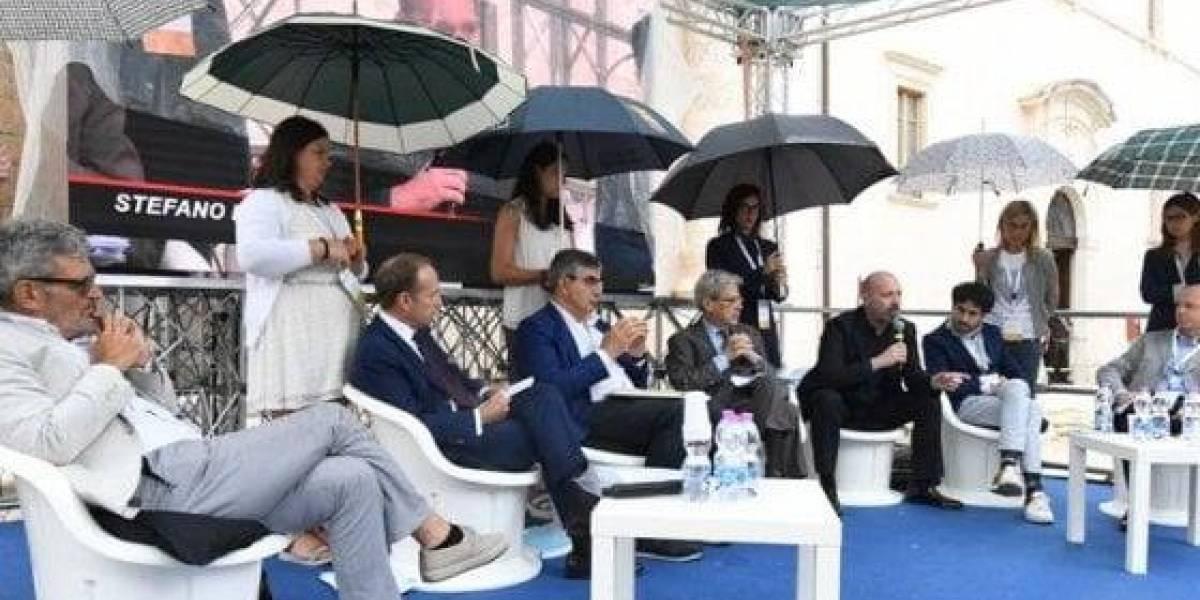 La imagen que causa polémica en Italia: mientras ellos discuten, ellas sostienen los paraguas