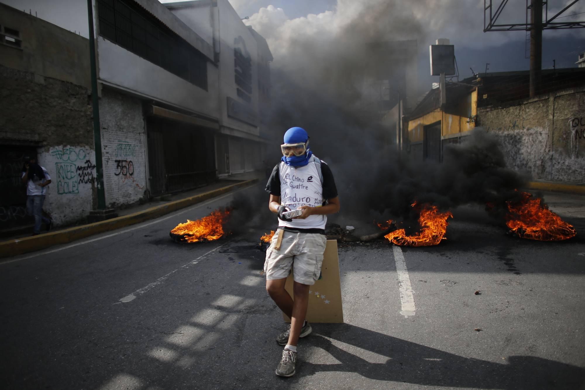 Un manifestante anti-gobierno descansa sobre su escudo en un bloque de carreteras, durante una protesta en Caracas, Venezuela, hoy jueves 6 de julio de 2017. Las protestas de la oposición exigen nuevas elecciones y denuncian inflación de tres dígitos, esc
