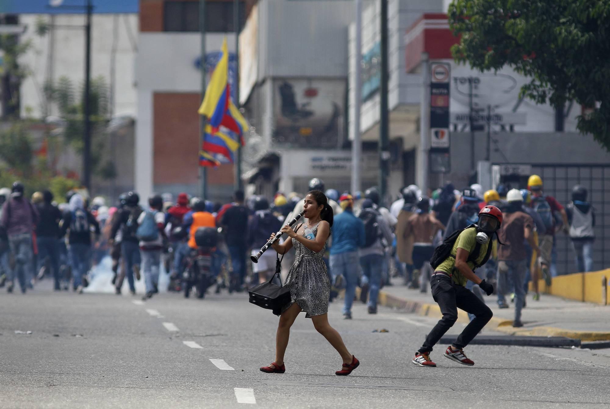 Una mujer joven toca su clarinete en medio de enfrentamientos entre manifestantes antigubernamentales y fuerzas de seguridad, durante una protesta en Caracas, Venezuela, hoy jueves 6 de julio de 2017. (Foto AP / Ariana Cubillos)