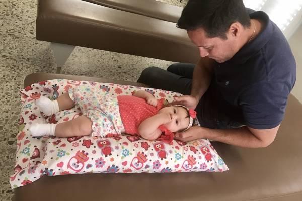El quiropráctico Oscar Otero evalúa una bebé de un mes de nacida. / Suministrada