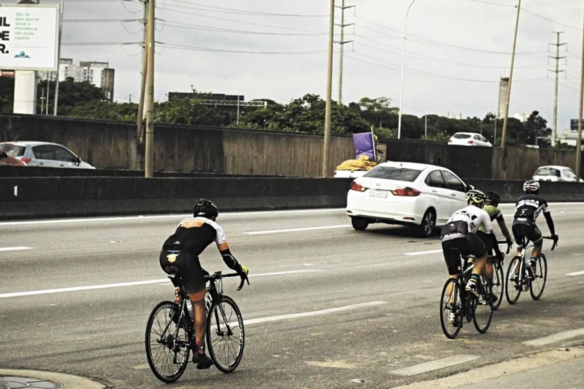 Na imagem, uma avenida sem acostamento ou ciclovia. Nela, ciclistas ocupam a faixa da extrema direita.