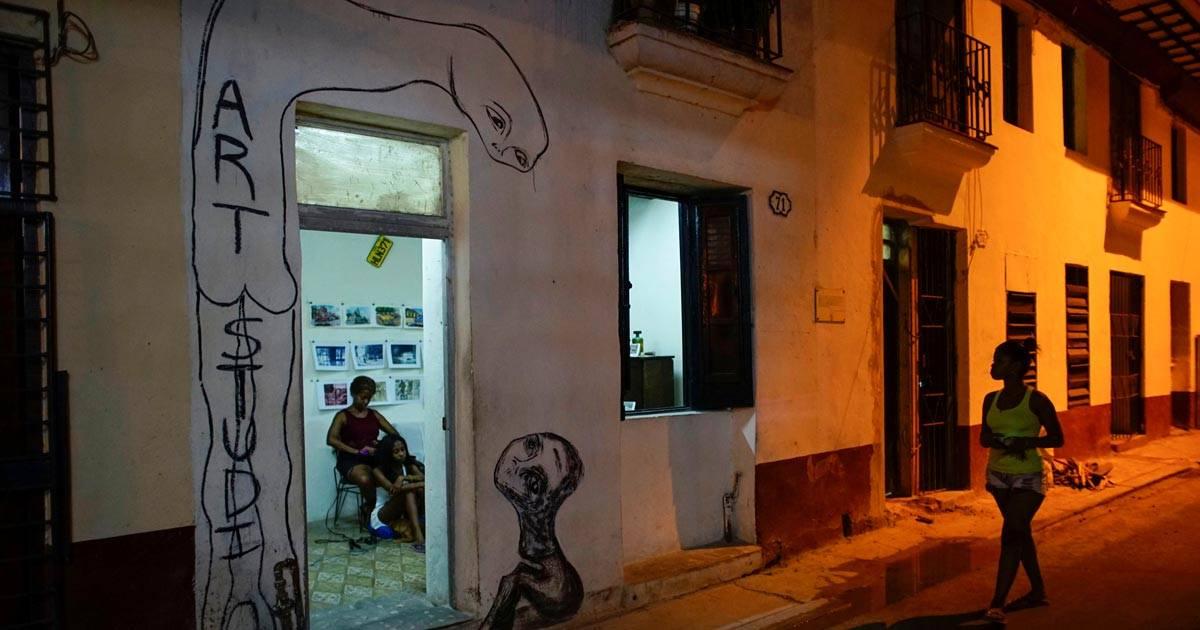 Mulher passa em frente a uma galeria de arte decorada com o grafite do artista cubano Yulier Rodriguez, em Havana REUTERS/Alexandre Meneghini