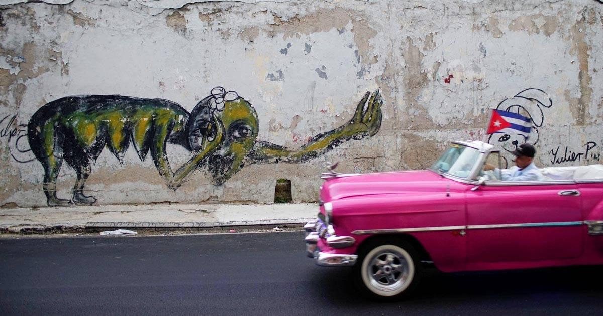 Carro passa em frente ao grafite do artista cubano Yulier Rodriguez, em Havana REUTERS/Alexandre Meneghini