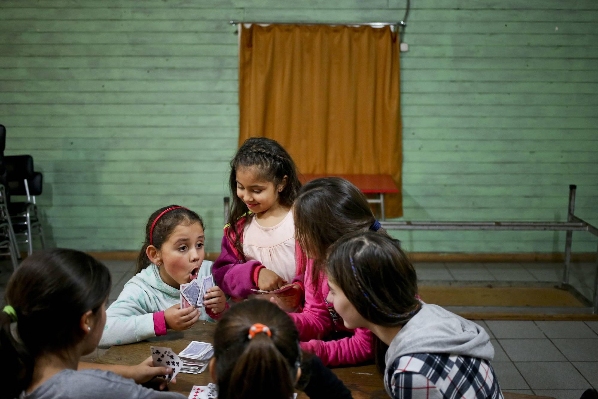 En esta imagen del 30 de de junio de 2017, la niña transgénero Selenna, a la izquierda, juega a las cartas durante un receso con otras niñas en una clase de danza en su centro comunitario en Santiago de Chile. La madre de Selenna, Evelyn Silva, dijo que h
