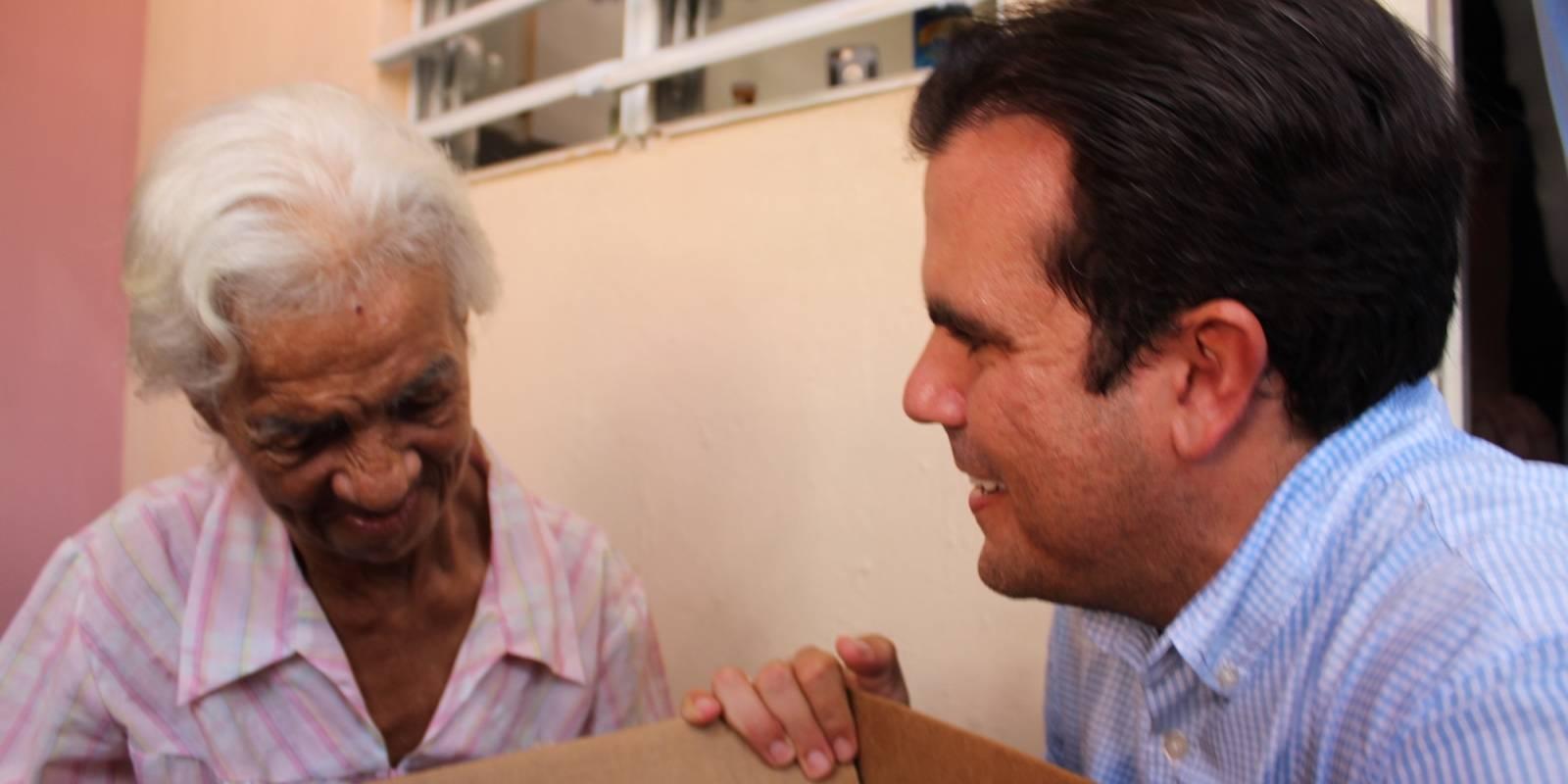 Eroína Camacho, de 72 años, recibe una caja con alimentos. / David Cordero Mercado
