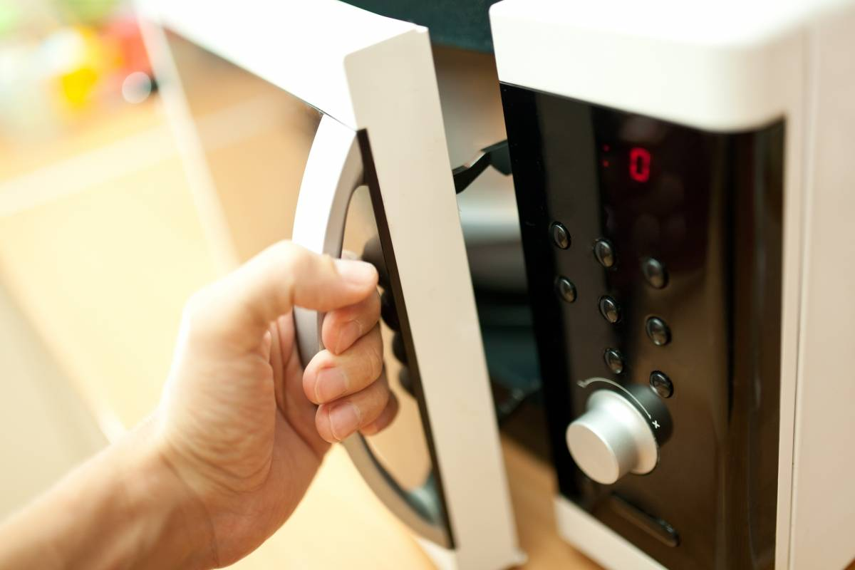 Hand of person opening a microwave oven