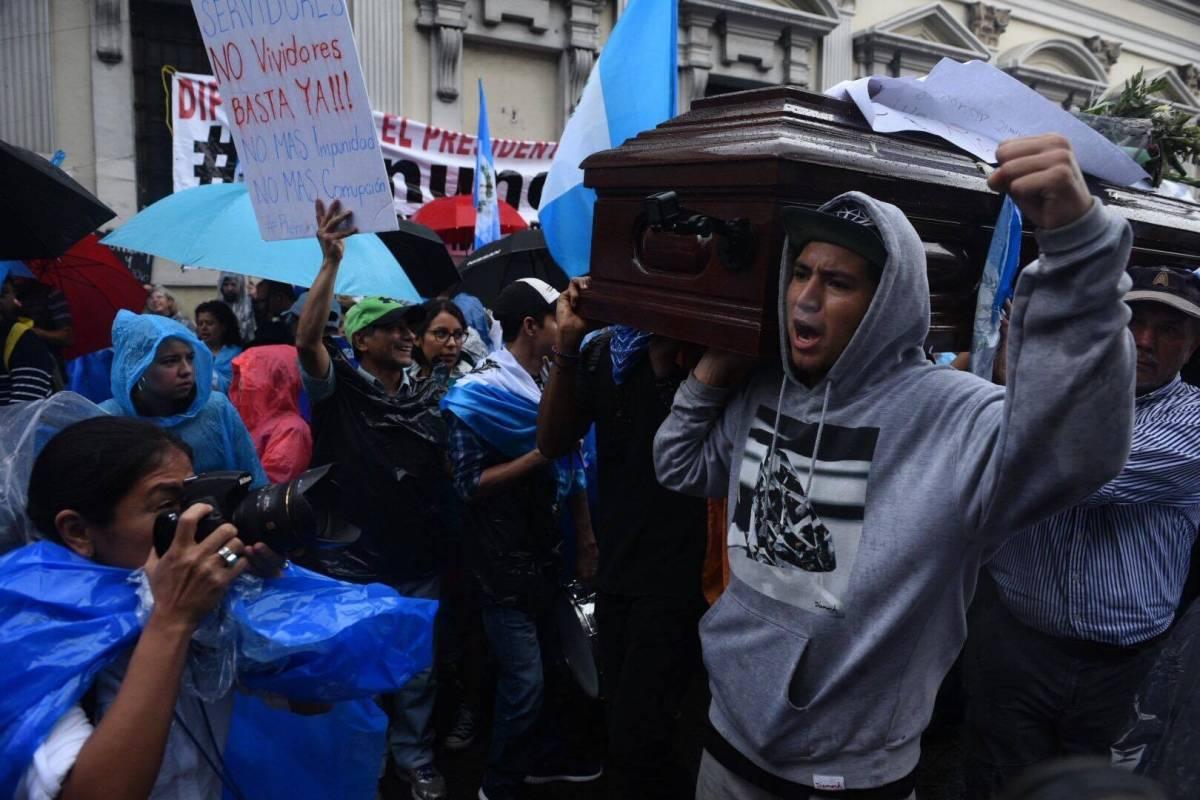 Manifestantes cargan ataúd