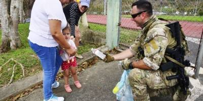 Una niña se muestra esquiva ante un efectivo de la Guardia Costera que quiere hacerle entrega de un botellón con agua.