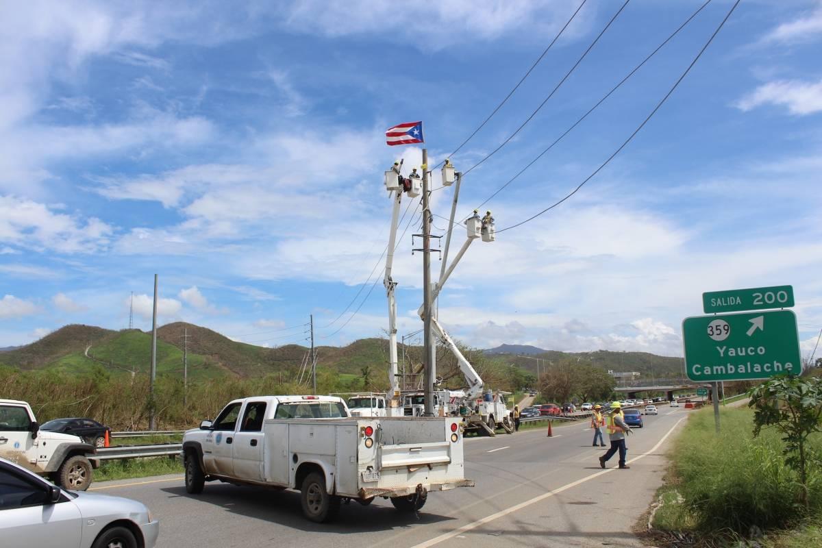 Empleados de la AEE colocaron una bandera de Puerto Rico al tope de un poste de la Autoridad en la carretera #2 en Yauco. / Foto: Miguel Dejesús