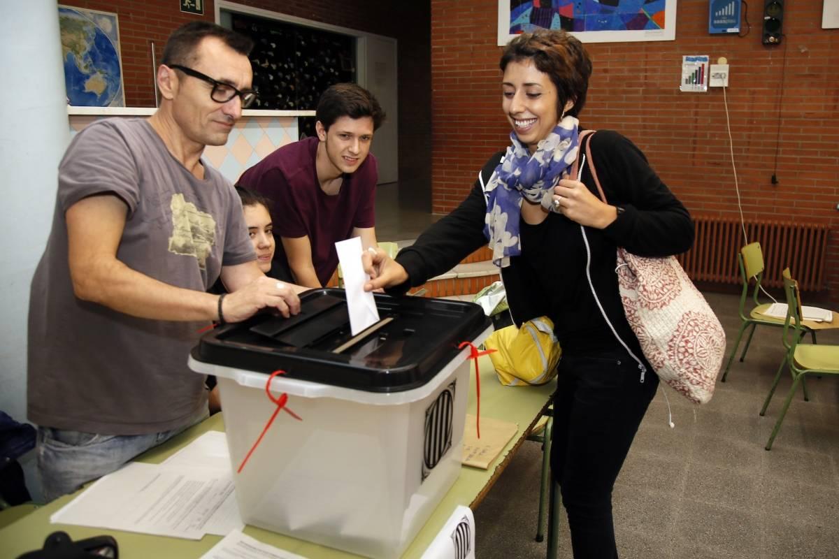 Una mujer emite su voto durante el referendo sobre la independencia de Cataluña el domingo 1ro de octubre en un centro de votación del barrio Gracia de Barcelona. Las urnas fueron compradas por internet en China y llegaron en secreto a través de Francia.