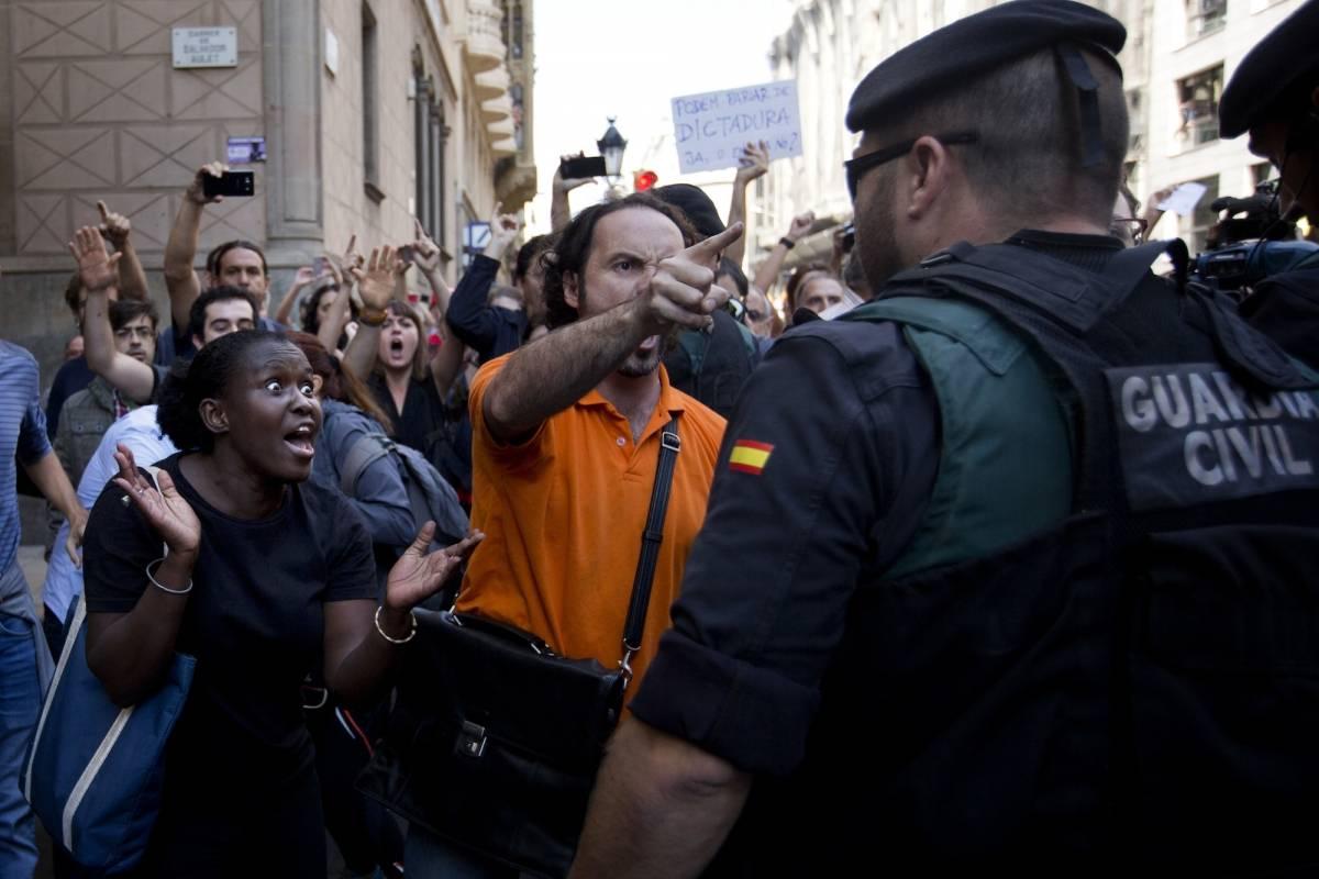 Manifestantes tratan de detener el auto que transporta a Xavier Puig, un alto funcionario del gobierno catalán, arrestado por la Guardia Civil en Barcelona, España, el miércoles 20 de septiembre de 2017. / AP