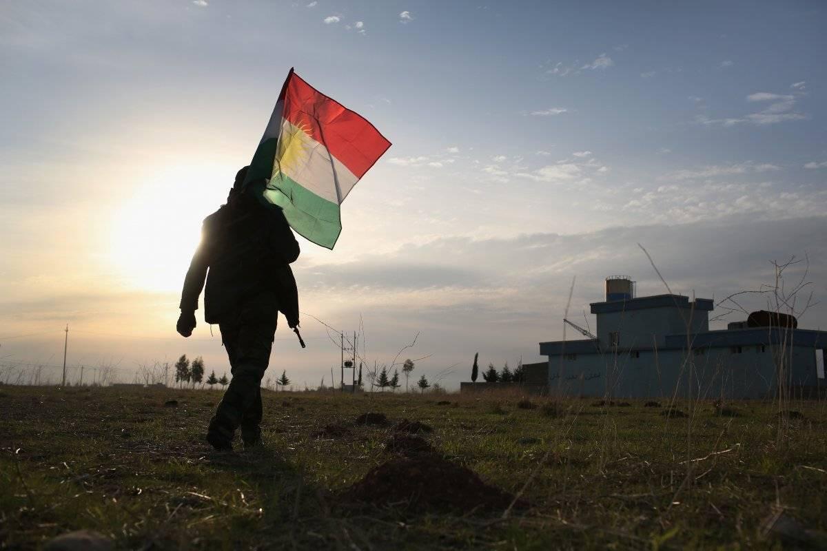 Un soldado peshmerga lleva la bandera de Kurdistán después de luchar contra el Estado Islámico.