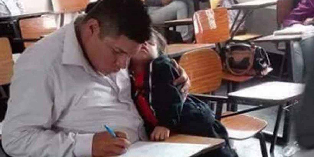 Viral imagen de padre tomando examen con su hijo en brazos