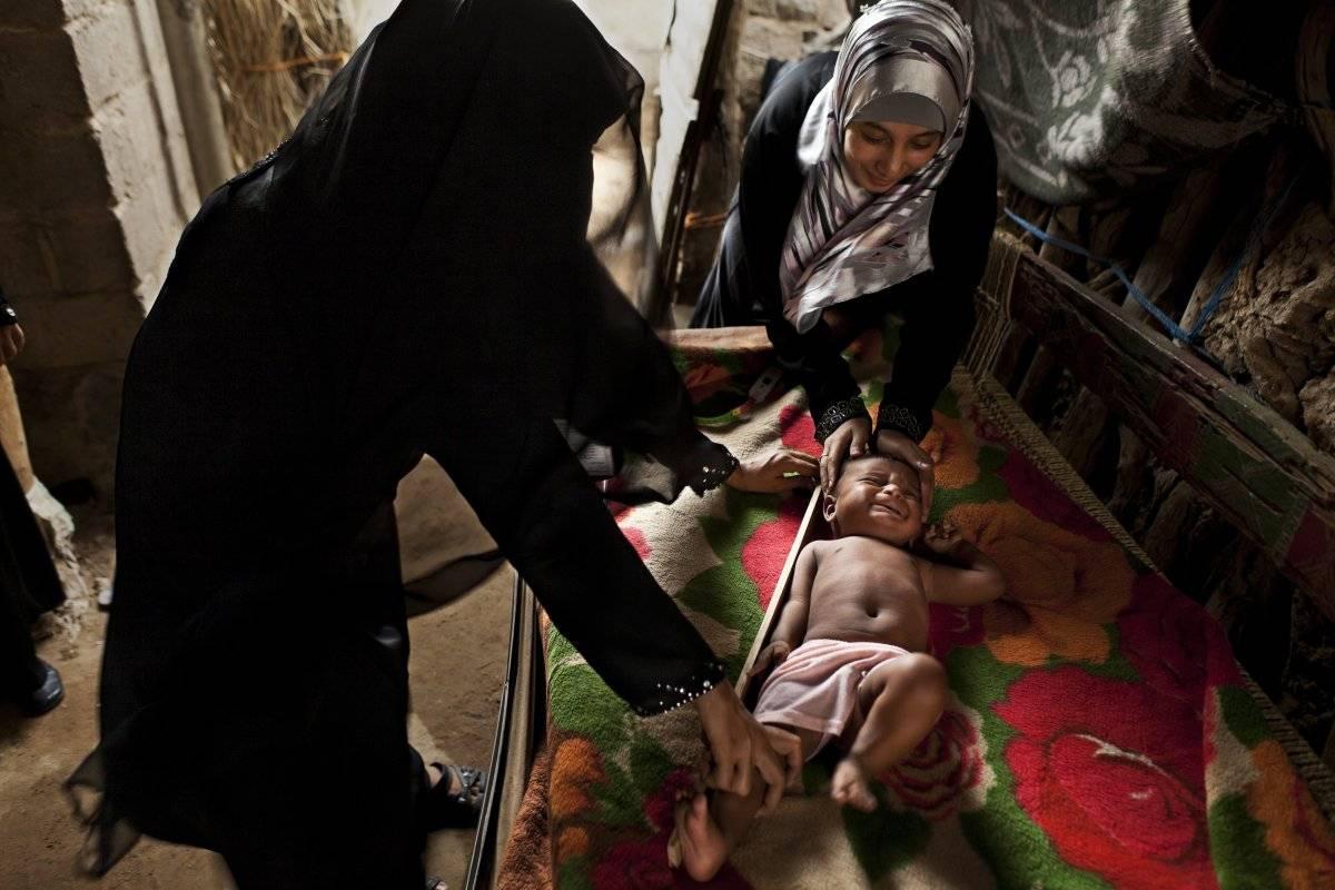 Dos mujeres cuidan a un niño en Yemén.
