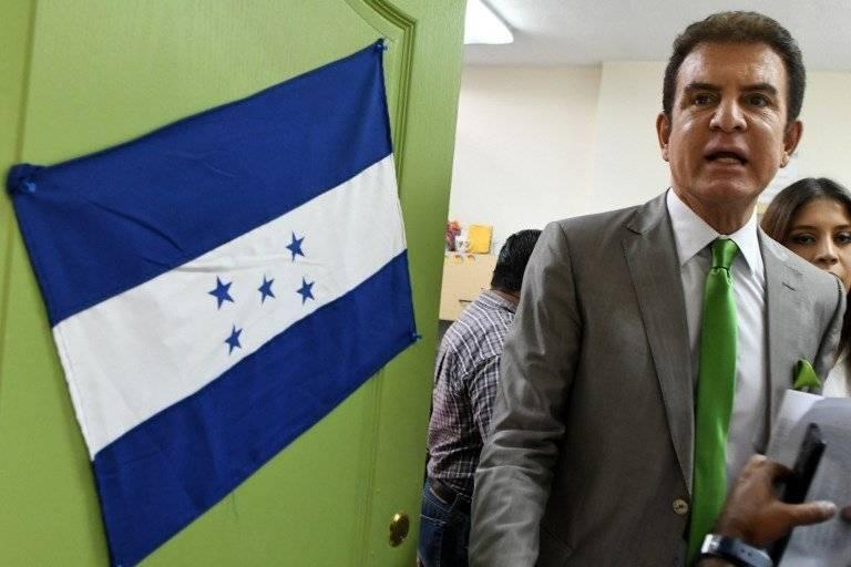 Salvador Nasralla junto a una bandera de Honduras