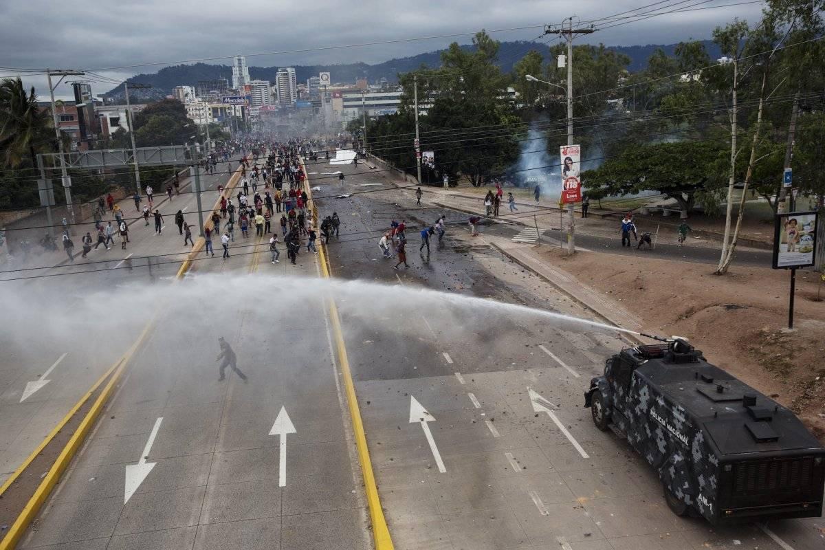 La policía lanza agua para dispersar a seguidores del candidato presidencial opositor Salvador Nasralla, reunidos cerca del lugar donde los votos de los comicios presidenciales están resguardados en Tegucigalpa, Honduras. (AP Foto/Rodrigo Abd)