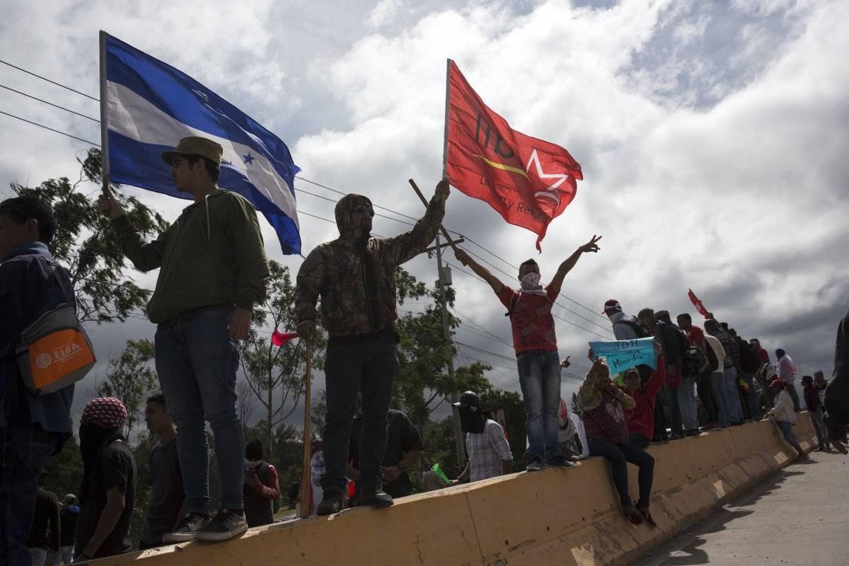Seguidores del candidato opositor Salvador Nasralla gritan consignas contra el gobierno cerca del lugar donde se guardan los votos de los pasados comicios presidenciales en Tegucigalpa, Honduras. (AP Foto/Rodrigo Abd)