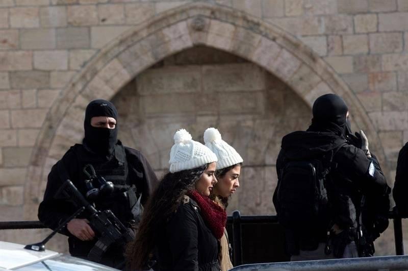 Dos muchachas palestinas pasan delante de dos policías israelíes que vigilan la Puerta de Damasco, en el casco viejo de Jerusalén