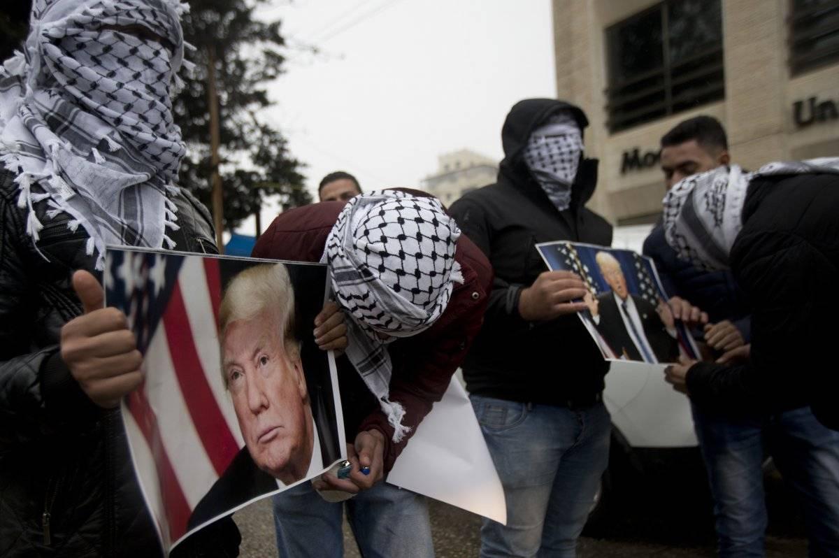 Los palestinos sostienen carteles del presidente estadounidense Donald Trump durante una protesta en Cisjordania, ciudad de Ramallah, el miércoles 6 de diciembre de 2017. / Majdi Mohammed-AP