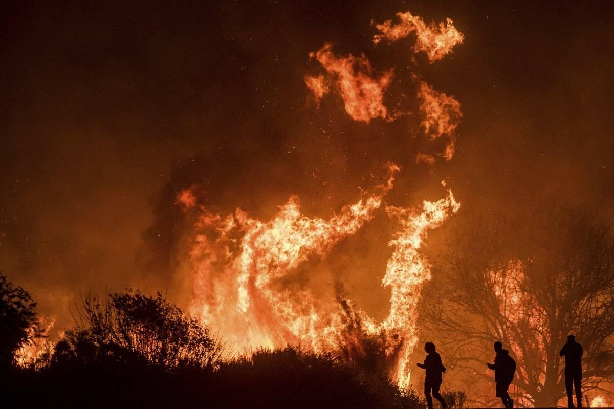 Varios conductores en la carretera 101 observan llamas del incendio Thomas que saltan sobre el camino al norte de Ventura, California, el miércoles 6 de diciembre de 2017. (AP Foto/Noah Berger)