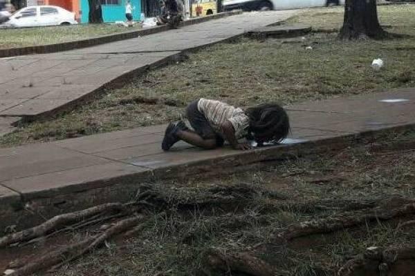 niña toma agua del suelo
