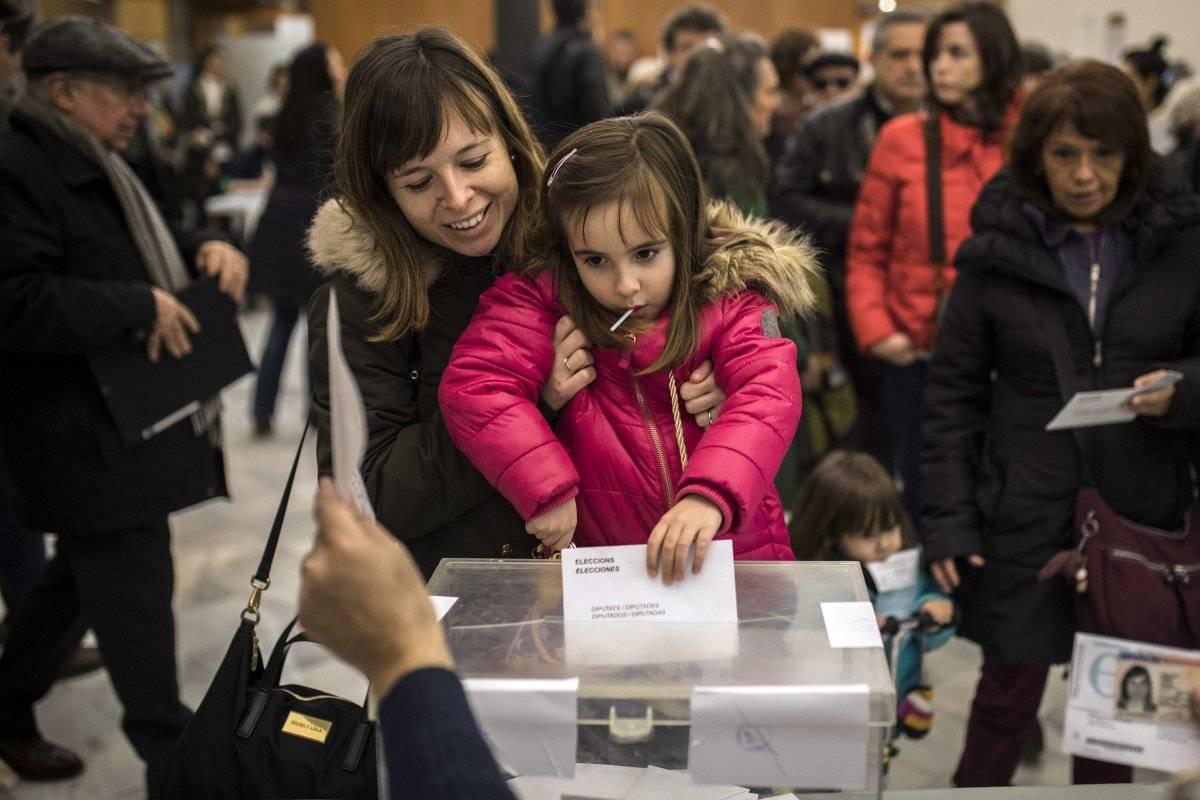 Una mujer sostiene a su hija para que meta su papeleta en la urna en un centro electoral durante las elecciones regionales de Cataluña, en Barcelona, España, el jueves 21 de diciembre de 2017. (Foto: AP/Santi Palacios)