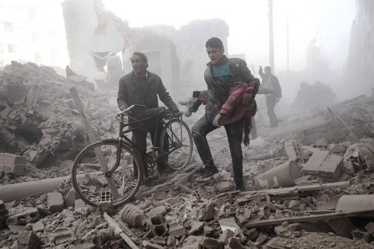 Joven sirio carga a un niño