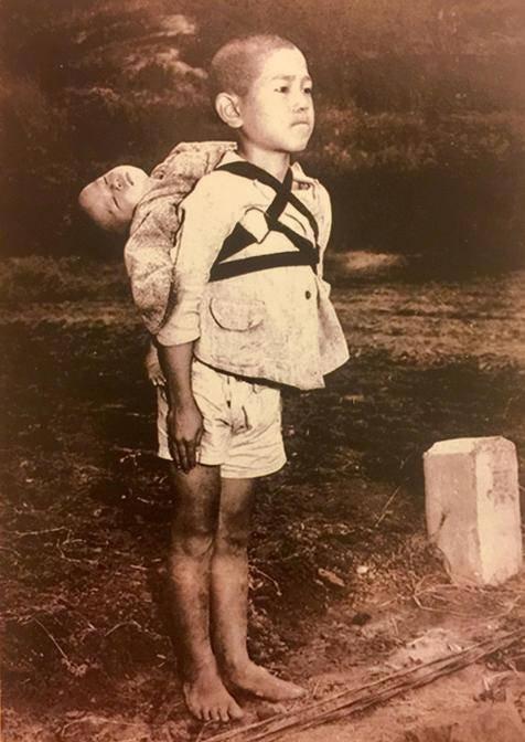 Foto mostra bebê morto sendo levado por irmão após ataque nuclea