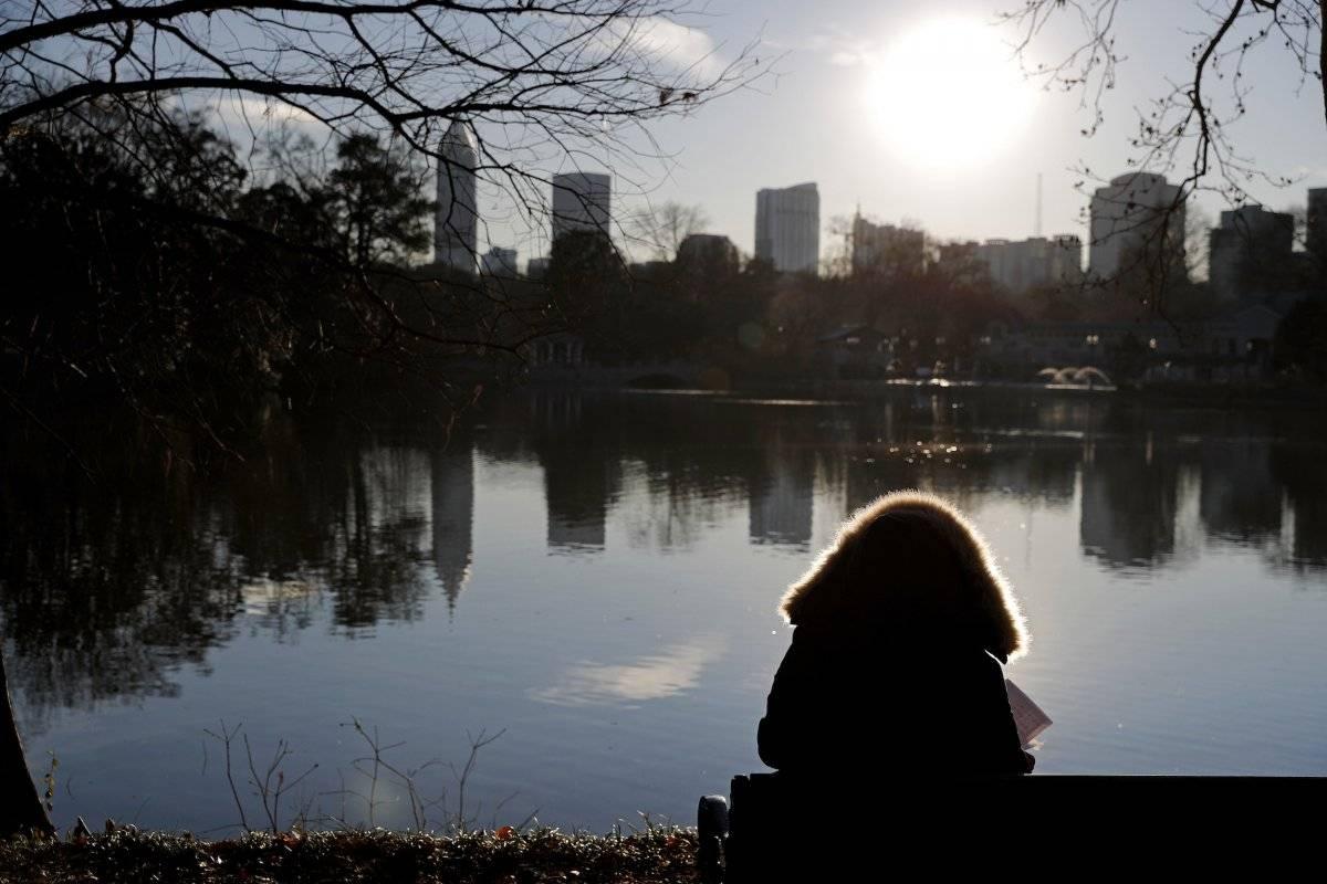 Una persona está sentada con su abrigo invernal mientras observa los edificios de Atlanta, el martes 2 de enero de 2018. (AP Foto/David Goldman)