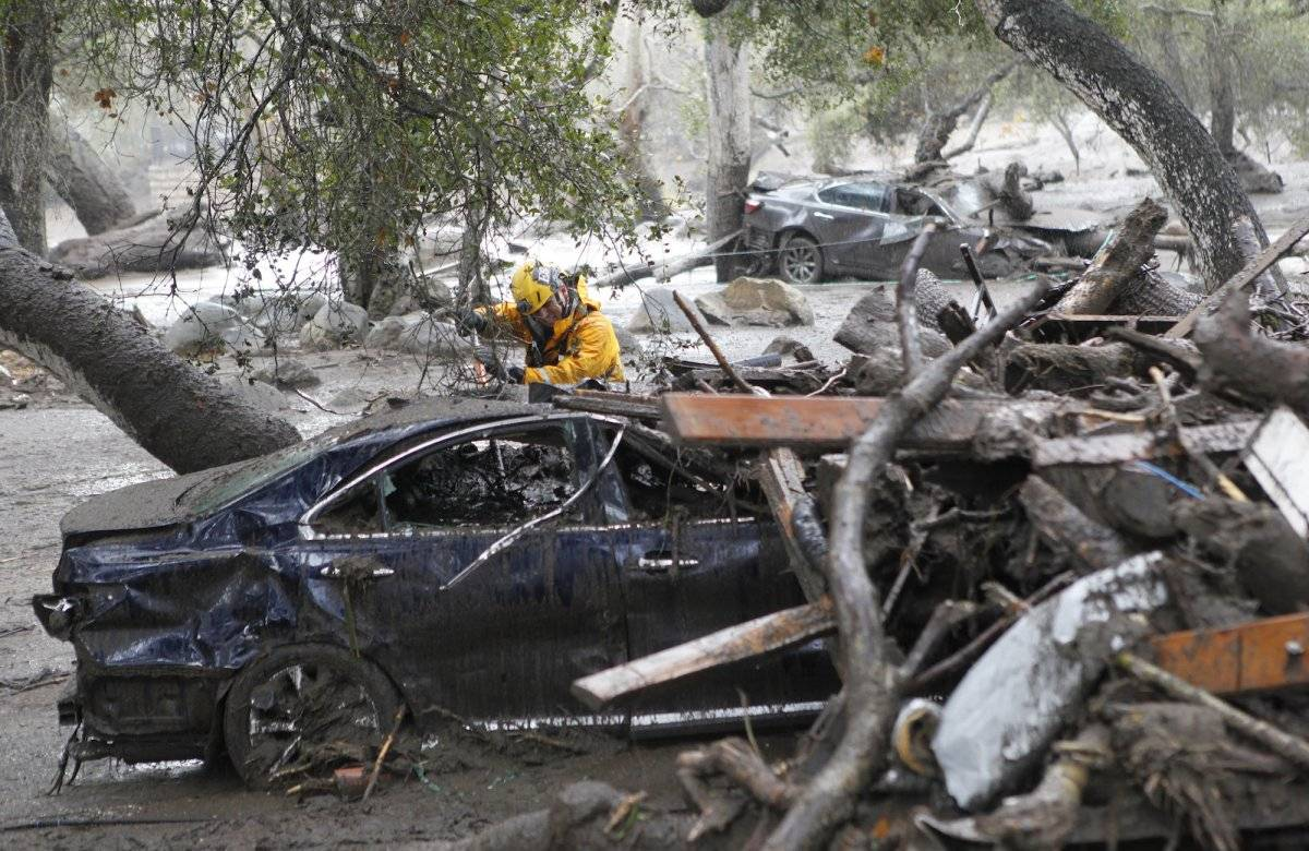 Un miembro del equipo de búsqueda y rescate de Long Beach busca sobrevivientes dentro de un automóvil en Montecito, California, el martes 9 de enero de 2018. (Daniel Dreifuss)