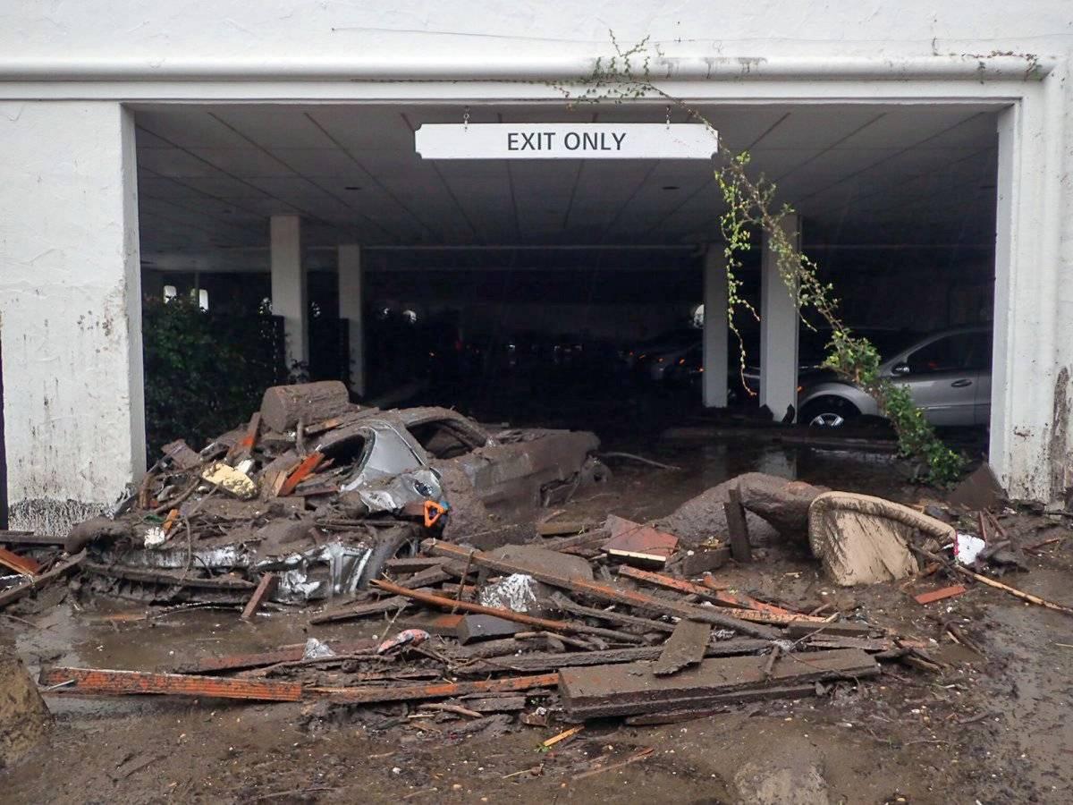 Fotografía facilitada por los bomberos del condado de Santa Bárbara muestra vehículos dañados luego de ser arrastrados por corrientes de lodo y escombros en el estacionamiento del hotel The Montecito Inn en Montecito, California, el martes 9 de enero de 2