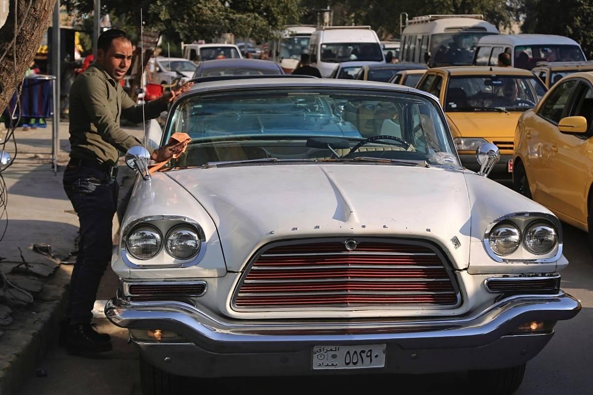 Un hombre le saca brillo a un Chrysler de 1952 estacionado frente a la cafetería de Saad al-Nuaimi el 10 de enero del 2018 en Bagdad. Los autos viejos recuerdan tiempos mejores a los iraquíes. (AP Photo/Khalid Mohammed) AP
