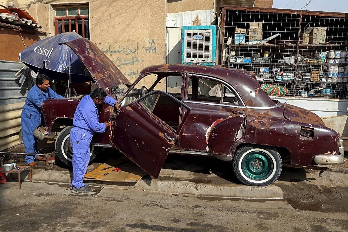 Dos mecánicos trabajan en un Chevrolet de 1952 propiedad de Saad al-Nuaimi el 11 de enero del 2018 en Bagdad. (AP Photo/Karim Kadim) AP