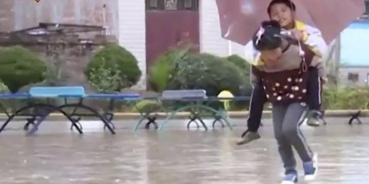 """""""Nunca lo dejaré atrás. Seré su bastón para siempre"""": niña china de 9 años lleva todos los días a la escuela a su hermano con movilidad reducida"""