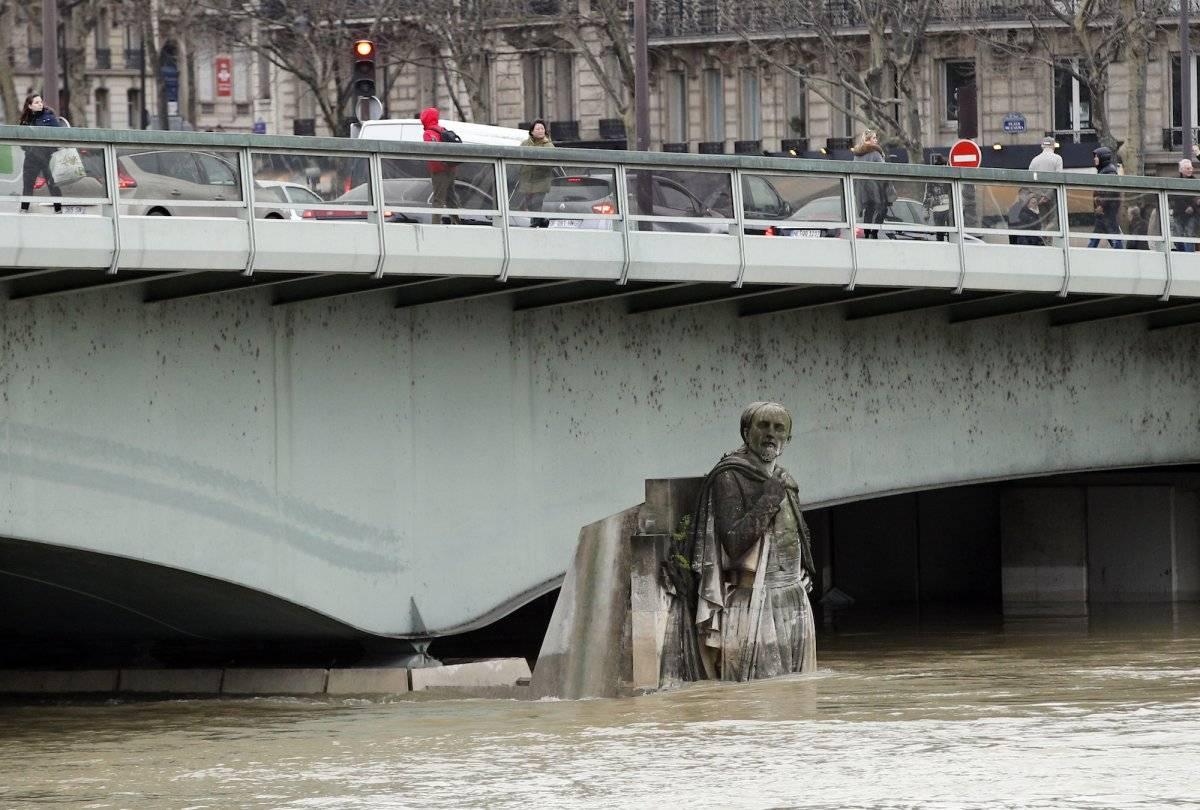 En esta fotografía del jueves 25 de enero de 2018, la gente camina sobre el puente del Alma a la altura de la estatua Zouave, la cual sirve como un instrumento de medición durante las inundaciones en París. (AP Foto/Christophe Ena)