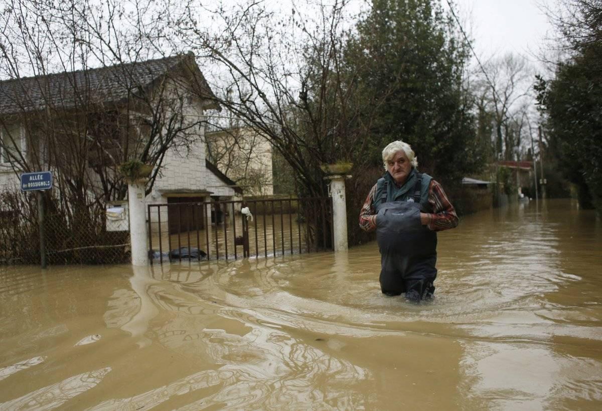 Una persona camina en una calle inundada en el este de París el jueves 25 de enero de 2018. (AP Foto/Thibault Camus)