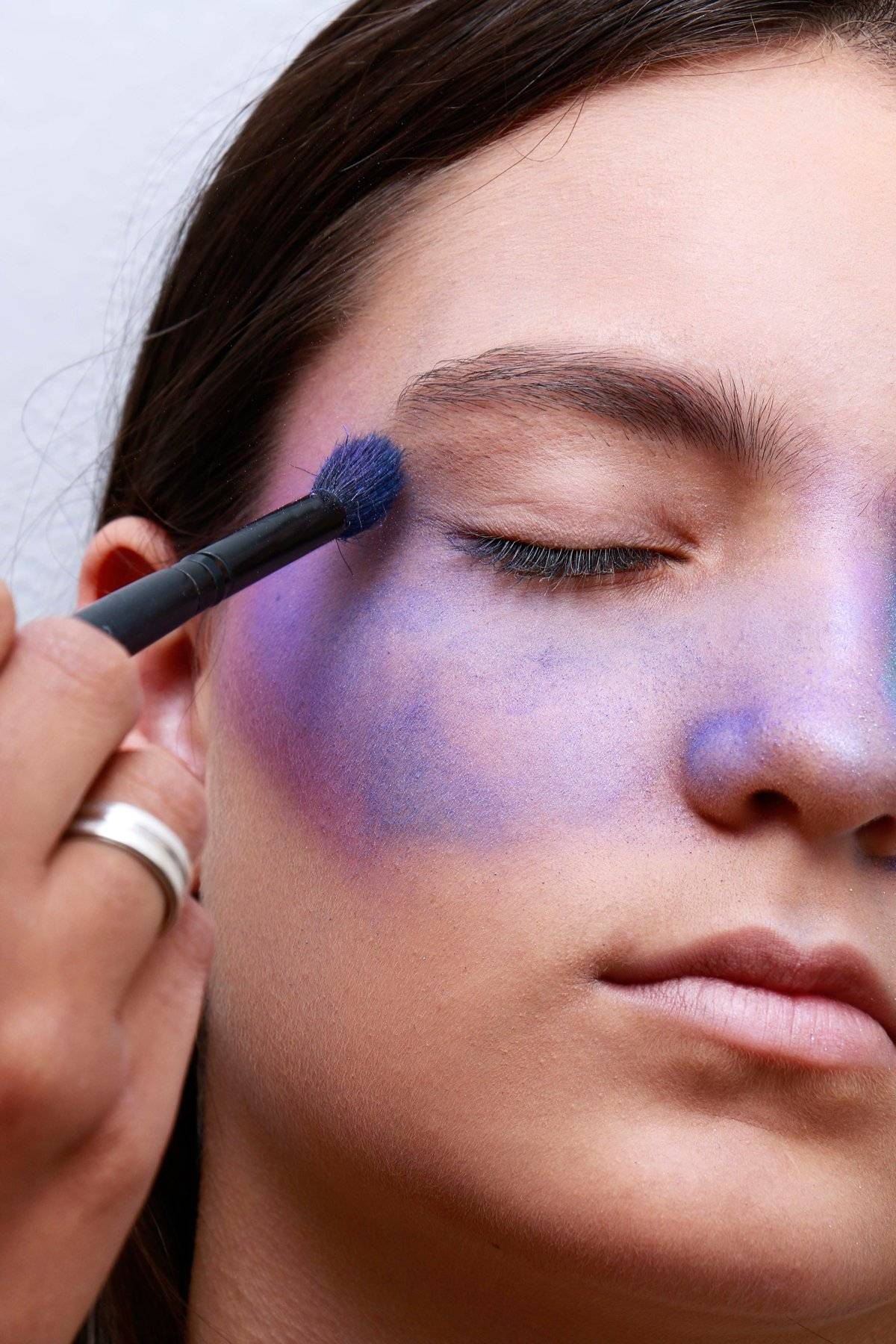 Prepare a pele. Uniformize o rosto com base e inicie o contorno com uma sombra roxa.