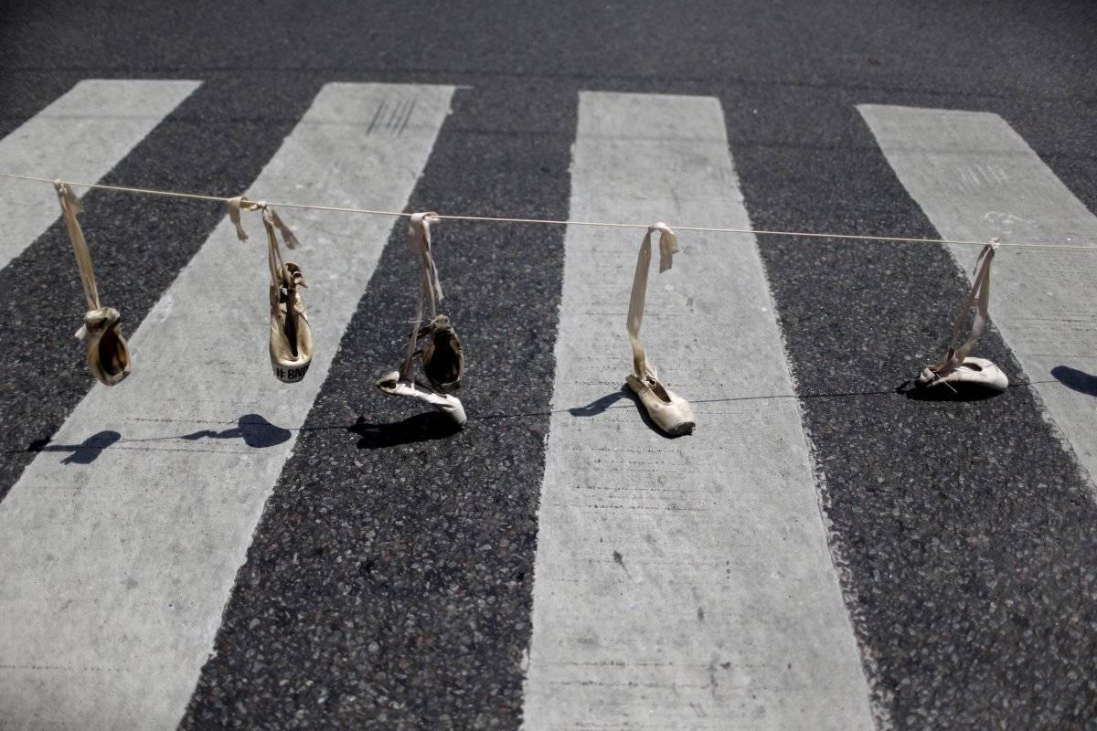 Zapatos de ballet cuelgan de una soga como parte de una protesta contra la reciente decisión de reducir los fondos para la compañía de danza estatal, en Buenos Aires, Argentina. (AP Foto / Natacha Pisarenko)