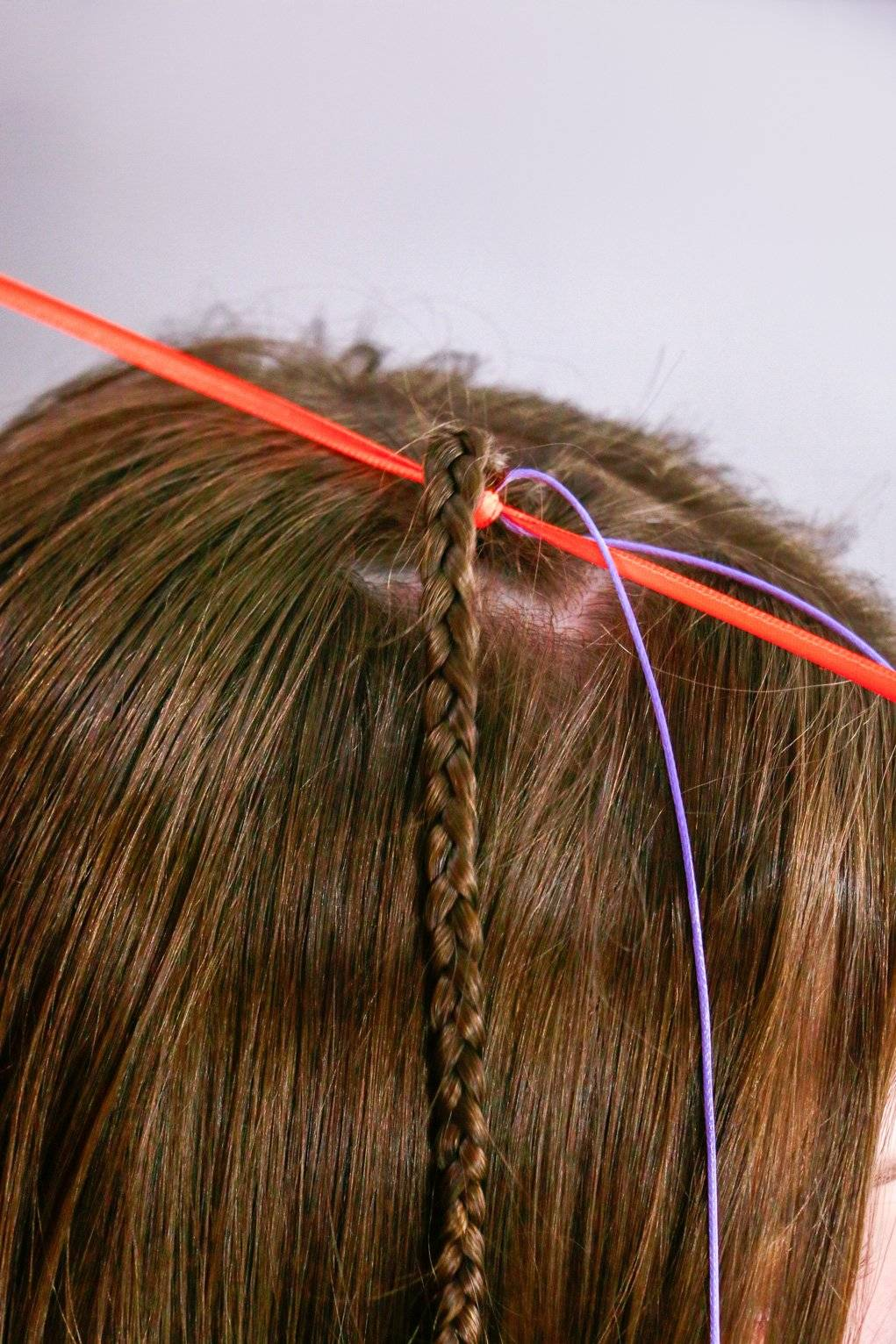 Faça um laço com a fita na raiz da trança, coloque a linha no meio e puxe bem João Guizze/ Divulgação