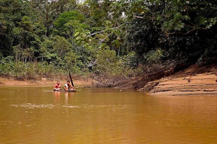 Familia kichwa navegando por el río Tiputini en canoas construidas a mano por los indígenas.
