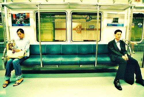 koreanmanandwomansittingapartonsubway.jpg