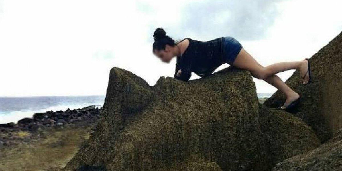 """Turista quiso tener la """"mejor foto"""" de su viaje pero causó indignación en Isla de Pascua: se acostó arriba de un moai"""