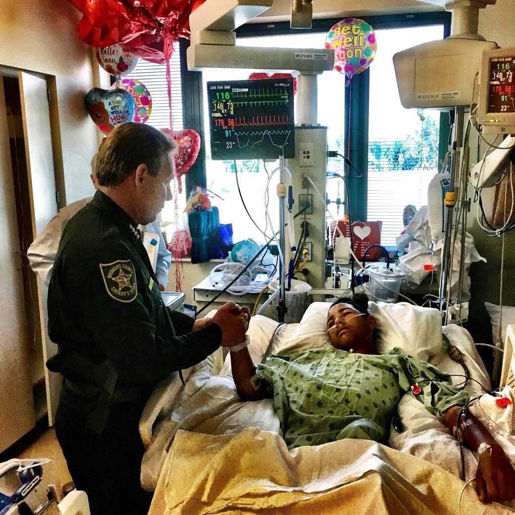 En esta foto del 18 de febrero de 2018, el jefe de policía del condado Broward, Scott Israel, sostiene la mano de Anthony Borges, un estudiante venezolano herido en el tiroteo del 14 de febrero en la escuela secundaria Stoneman Douglas. (Broward County Sh