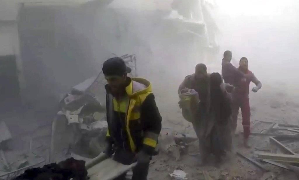 En esta imagen, tomada de un video publicado el 24 de febrero de 2018 por el grupo Defensa Civil Siria, también conocido como Cascos Blancos, muestra a voluntarios de la formación ayudando a residentes durante ataques aéreos y bombardeos de las fuerzas de